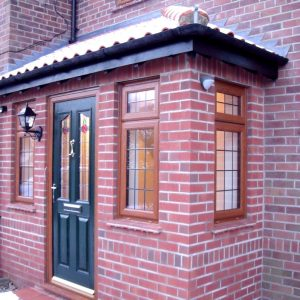 Full brick porch with double glazed windows in woodgrain finish